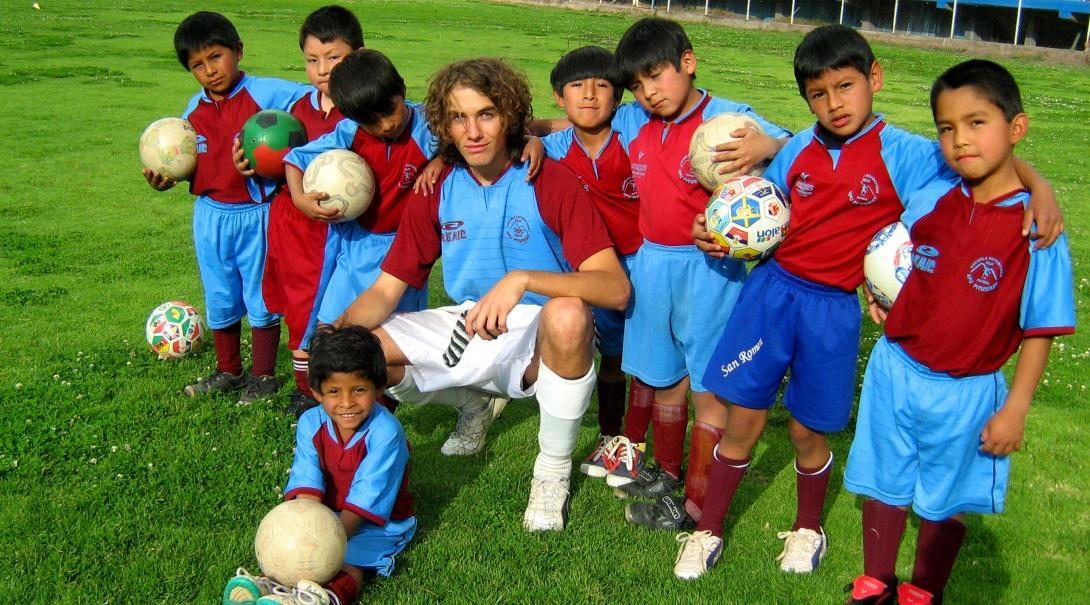 A sports instructor works with children during his volunteer sports coaching in Peru